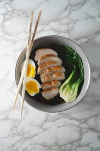 A grey bowl with chopsticks, broth, black noodles, bok choy, chicken, and eggs for a Asian Chicken noodle soup bowl