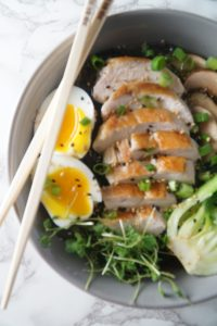 Half image of a while bowl with eggs, chicken, bok choy, mushrooms and chopsticks.