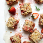 Strawberry Rhubarb crumble bars on a piece of parchment paper with fresh strawberries and mint