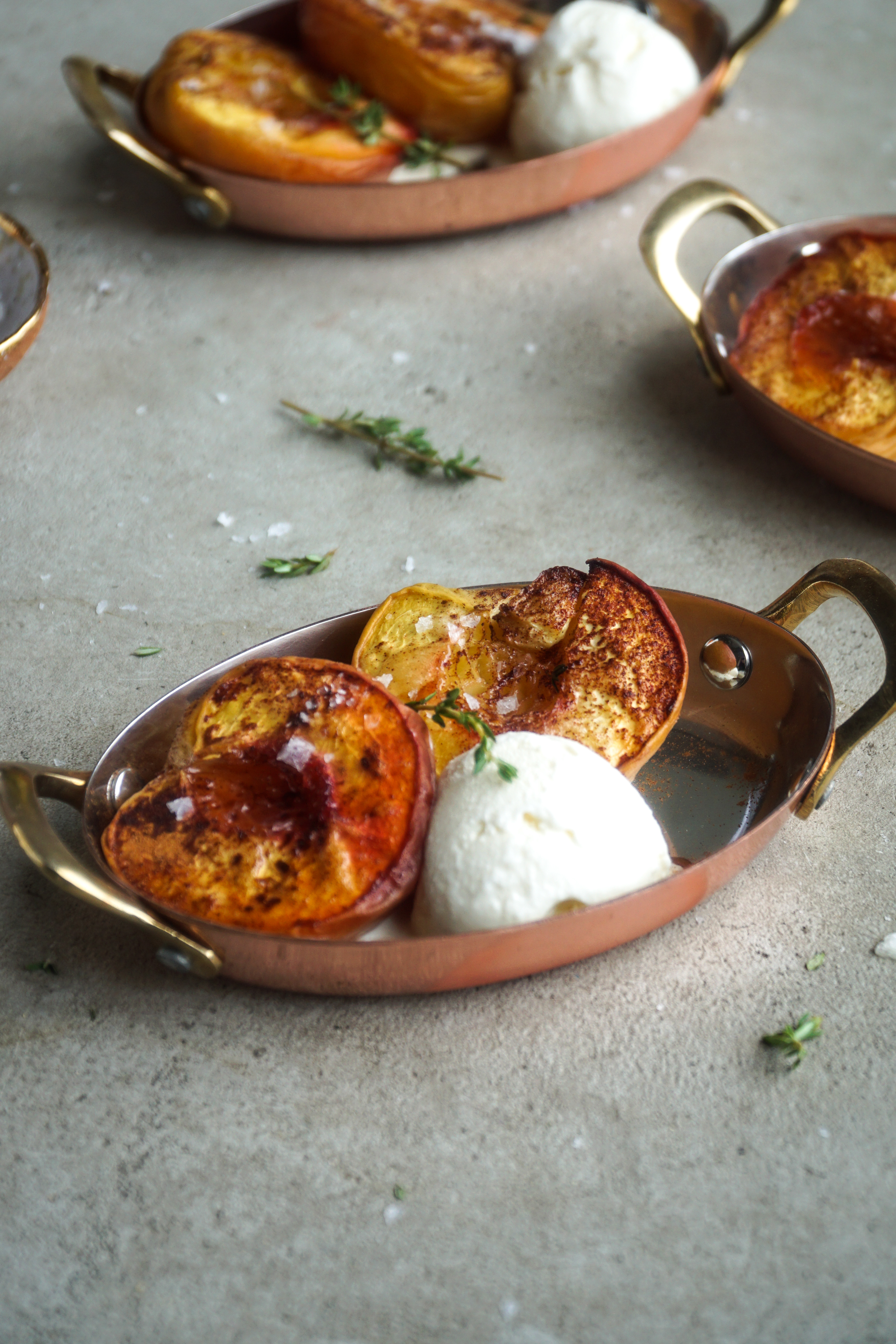 Dish with two peach halves and a scoop of ice cream with a sprig of thyme.