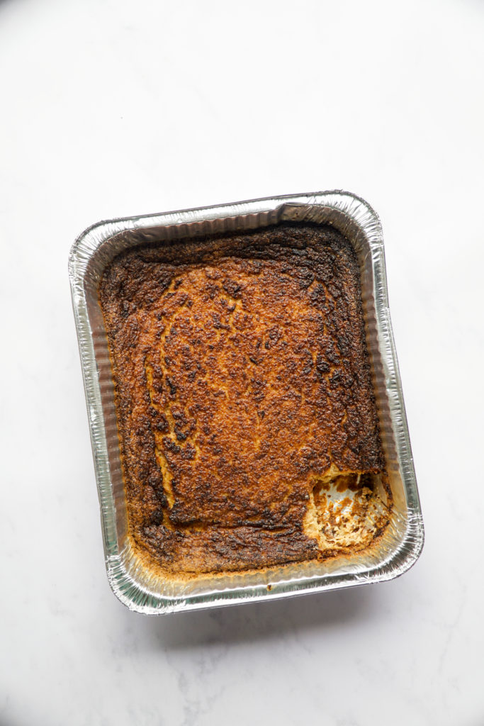 The best overnight potato kugel with a piece cut out.